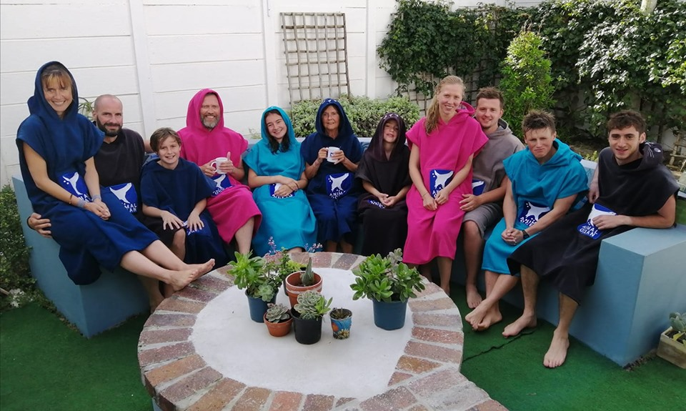 11 people sit together in Animal Ocean towel ponchos in the garden