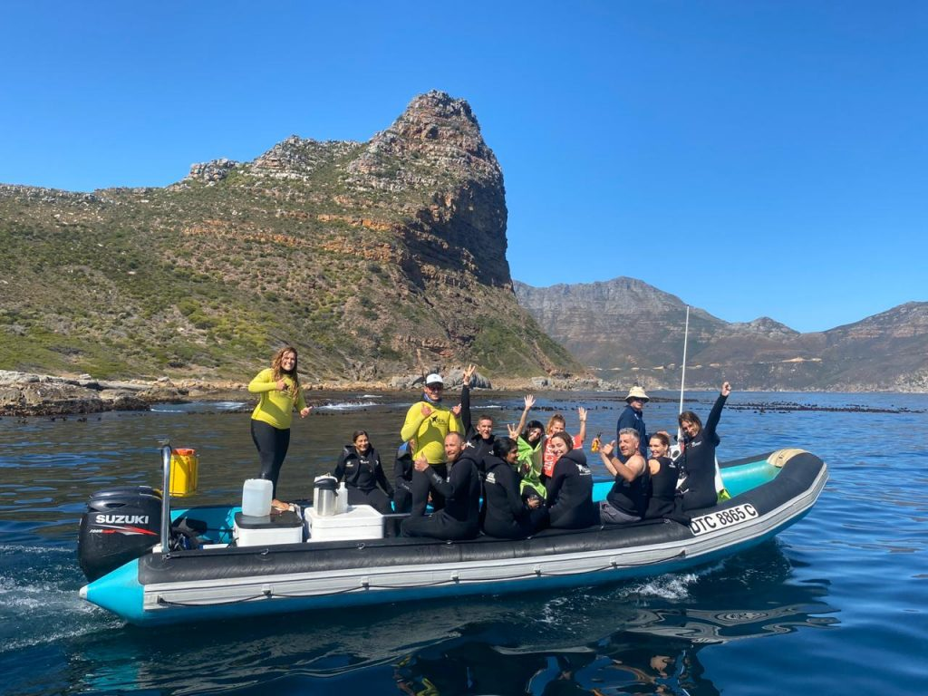 People in wetsuits sit on a boat smiling after Seal Snorkeling